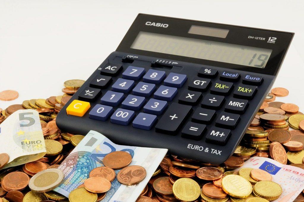 calculatrice posée sur un tas de pièces et de billets